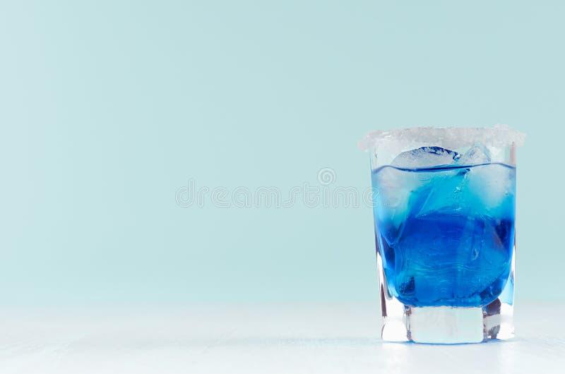 Kaltes blaues Lagunengetränk des Sommers mit Eiswürfeln, Salzkante im eleganten Schnapsglas auf tadellosem Pastellhintergrund stockbilder