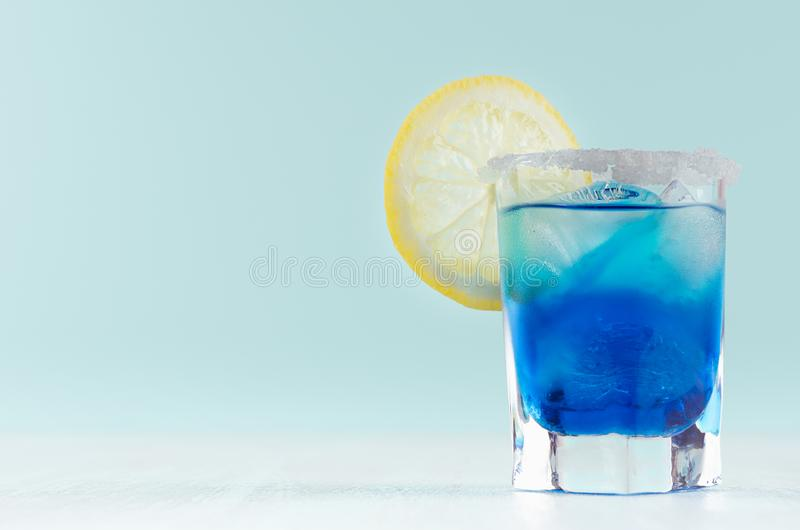Kaltes blaues Lagunengetränk des Sommers mit Zitronenscheibe, Eiswürfel, Salzkante im eleganten Schnapsglas auf tadellosem Pastel lizenzfreies stockbild