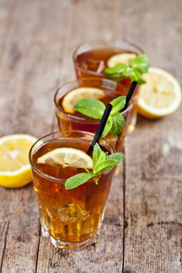Kaltes Eistee mit Zitrone, tadellosen Blättern und Eiswürfeln in drei Gläsern auf rustikalem Holztisch lizenzfreie stockbilder