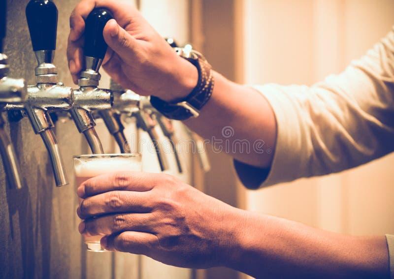 Kaltes Fassbier goss in Glas von der silbernen Bierzufuhr, selektiver Fokus lizenzfreies stockbild