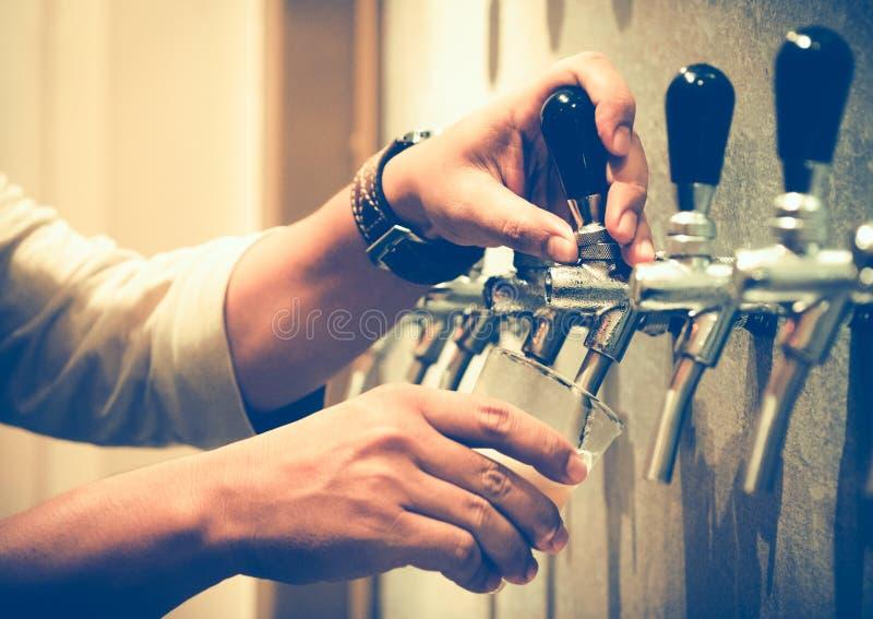 Kaltes Fassbier goss in Glas von der silbernen Bierzufuhr, selektiver Fokus stockfoto