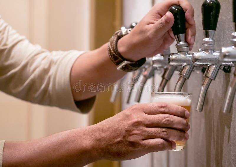 Kaltes Fassbier goss in Glas von der silbernen Bierzufuhr, selektiver Fokus stockbild