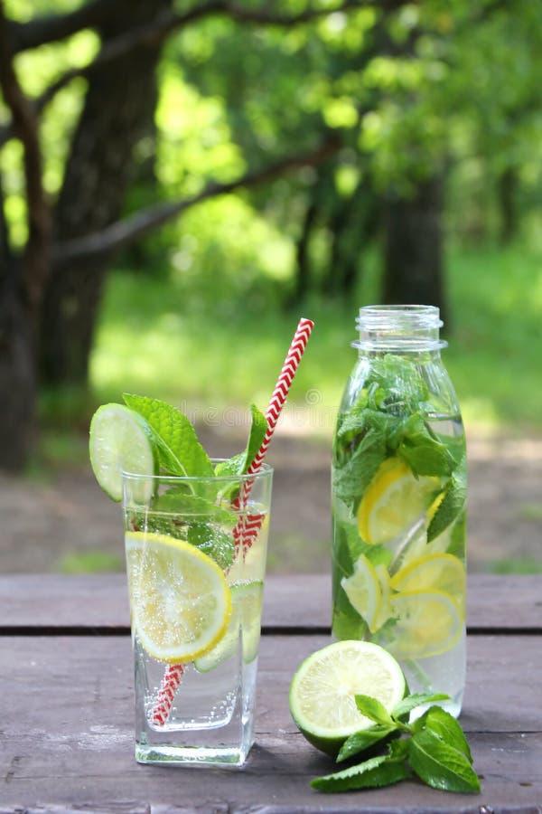 Kaltes Getränk der frischen Limonade im Glas und in der Flasche mit Zitronen, Kalk und Minze auf dem Holztisch im Freien lizenzfreie stockbilder