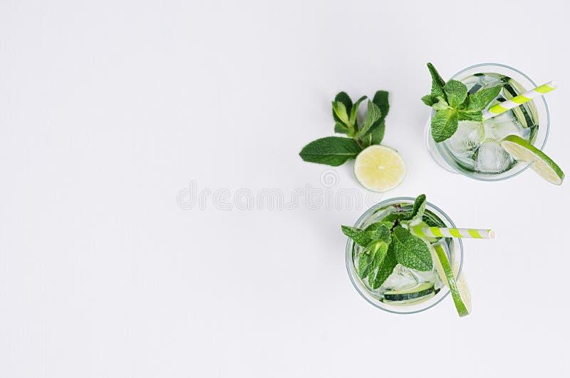 Kaltes Getränk des Sommers mit Eiswürfeln, Scheiben Kalk, Gurke, Stroh und Zweige prägen auf weißem hölzernem Brett, Draufsicht,  lizenzfreie stockfotos