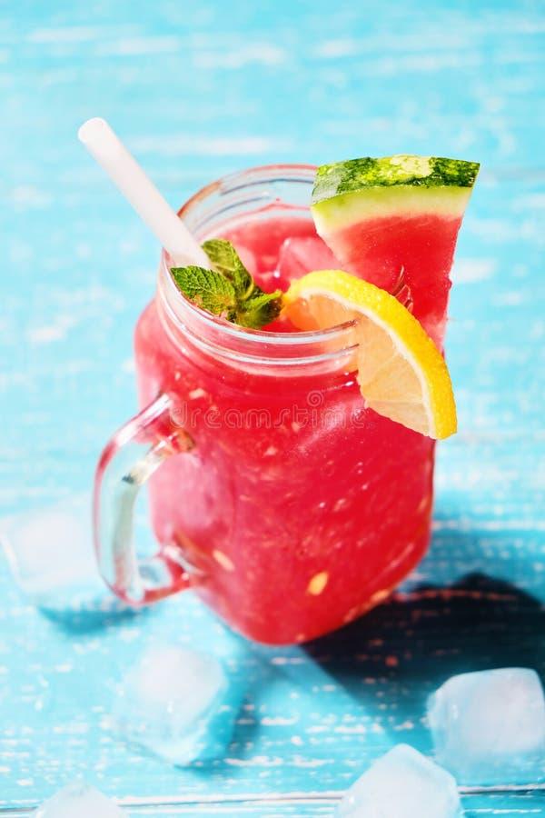 Kaltes Getränk des Sommers mit Wassermelone, Minze und Zitrone auf einem hölzernen Hintergrund stockbild