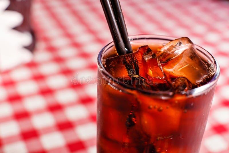 Kaltes Getränkgetränk Kolabaumsoda mit Eis und Blase auf rotem und weißem Hintergrund der Vorderansicht stockbilder