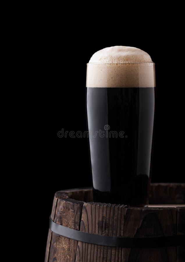 Kaltes Glas dunkles stout Bier auf hölzernem Fass lizenzfreie stockbilder