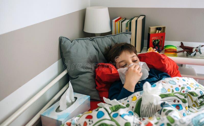 Kaltes Kind, das auf dem Bett liegt stockfotografie