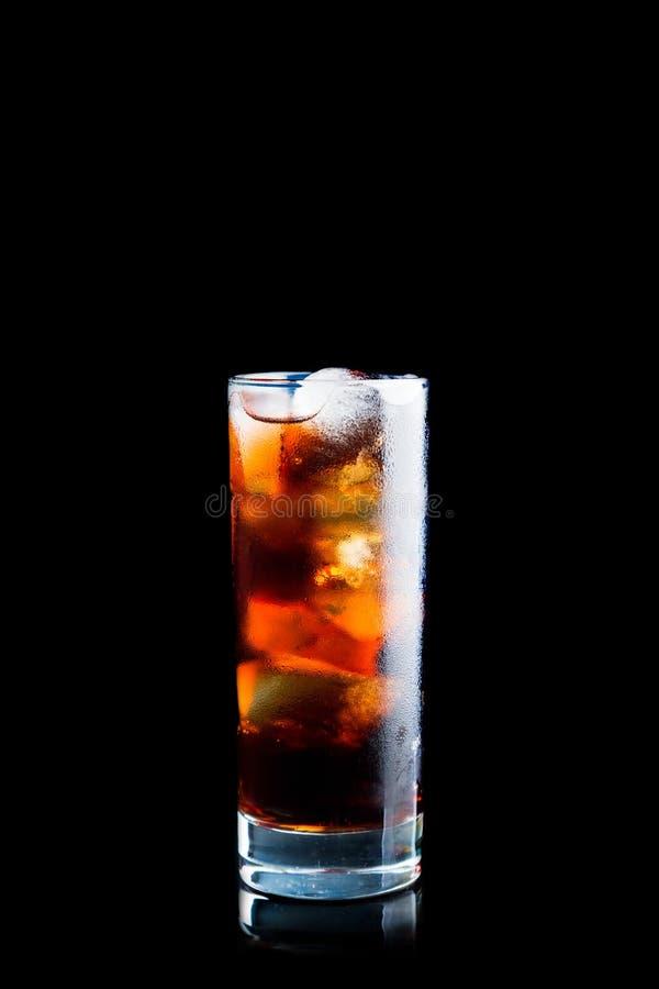 Kaltes Kolabaumgetränk im Glas mit dem Eis lokalisiert auf schwarzem Hintergrund lizenzfreie stockfotografie