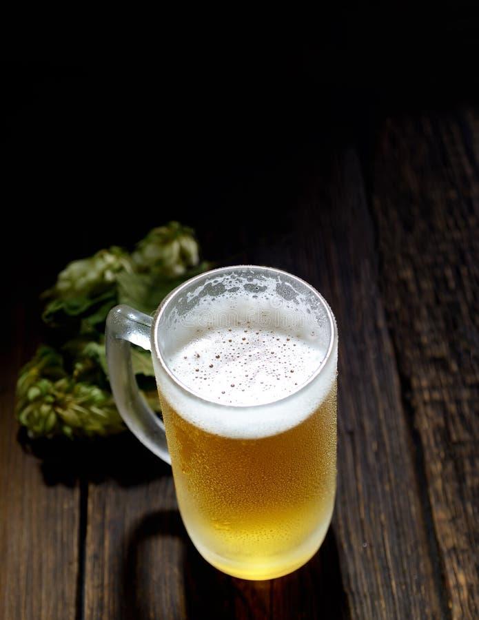 Kaltes schaumiges Bier in einem Glas und in den Hopfen auf einem dunklen hölzernen Hintergrund stockfotos