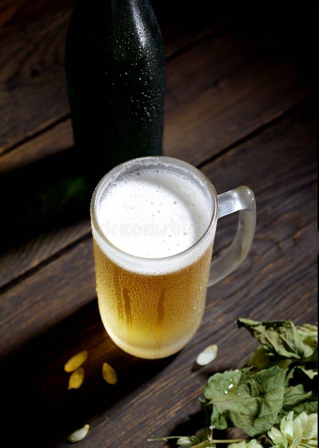 Kaltes schaumiges Bier in einer Glasflasche und in den Hopfen auf einem dunklen hölzernen Hintergrund lizenzfreies stockbild