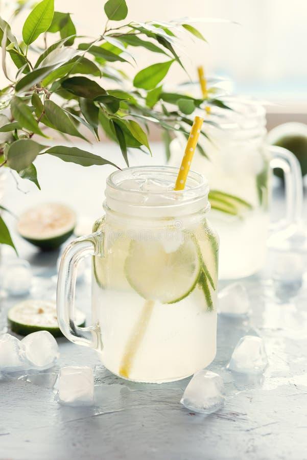 Kaltes und Auffrischungshineingegossenes Detox-Wasser mit Kalk in einer Glasgefäße geschmackvollen Kalk-Limonaden-Vertikale geton stockfotos