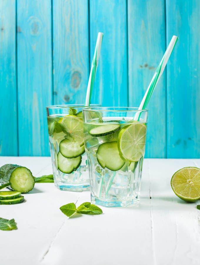 Kaltes und Auffrischungshineingegossenes Detoxwasser mit Kalk, Minze und Gurke in einem Glas auf hölzernem Hintergrund stockfotografie