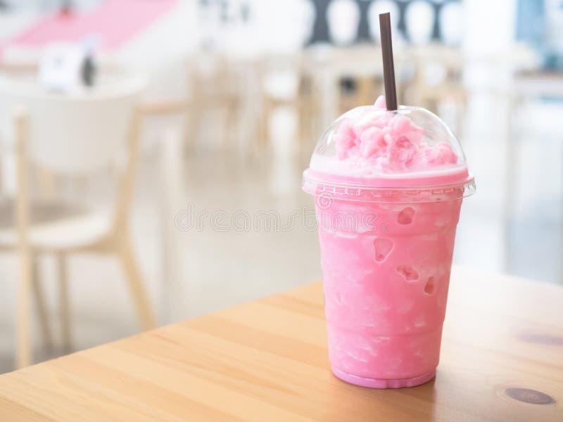 Kaltmilch-Smoothy in einer Plastiktasse auf einem Holztisch und hat Sonnenlicht auf einem schönen Hintergrund stockfotos