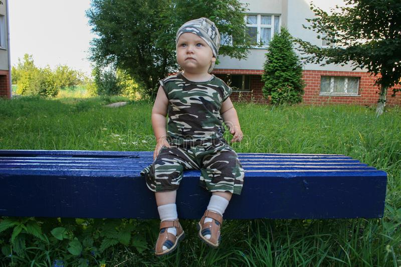 Little boy in camouflage clothes and camouflage bandana sitting on the blue bench. stock images