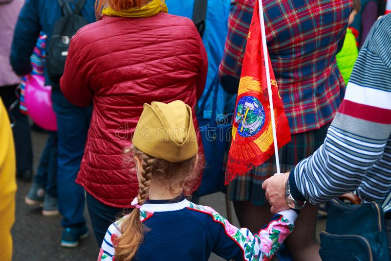 Kalugastad, Rusland - Mei 2019: het meisje die foerage-GLB met de rode vlag van de USSR dragen neemt aan herdenkingsparade deel stock foto's