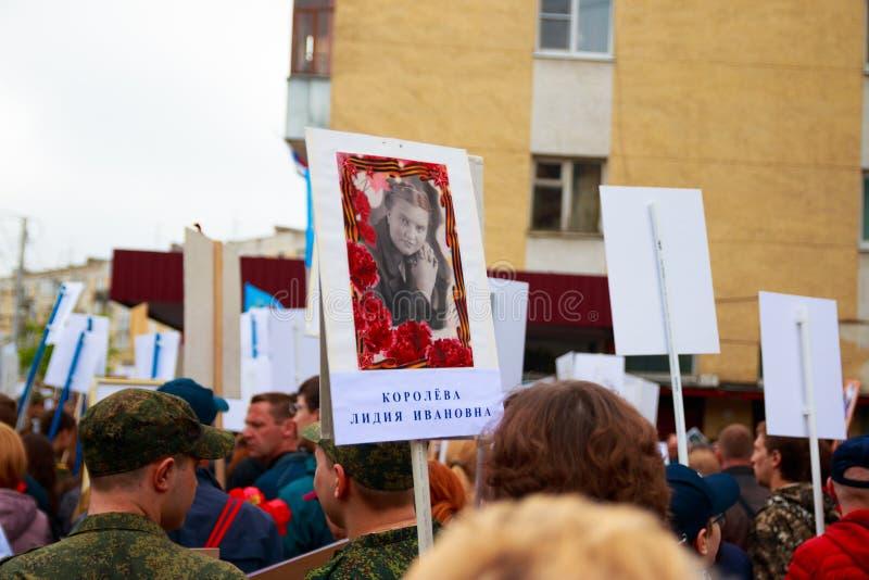 Kalugastad, Rusland - Mei 2019: plaat met naam en foto van jonge vrouw, oorlogsveteraan Vele mensen nemen aan herdenkingsparade d stock afbeeldingen