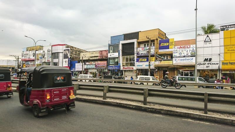 Kalutara, Sri Lanka - 24 de janeiro de 2017: Fragmento da vida urbana - construções, propaganda, estrada de cidade, transporte fotografia de stock