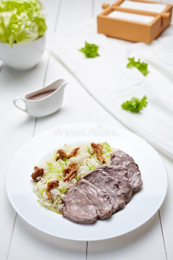 Kalvköttnötkött med ris, kräm- sås, grönsaker och champinjoner arkivbild