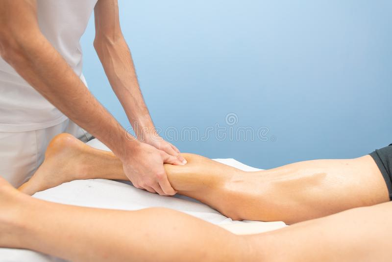Kalvmassage till en idrottsman nen av en yrkesmässig fysioterapeut royaltyfri foto