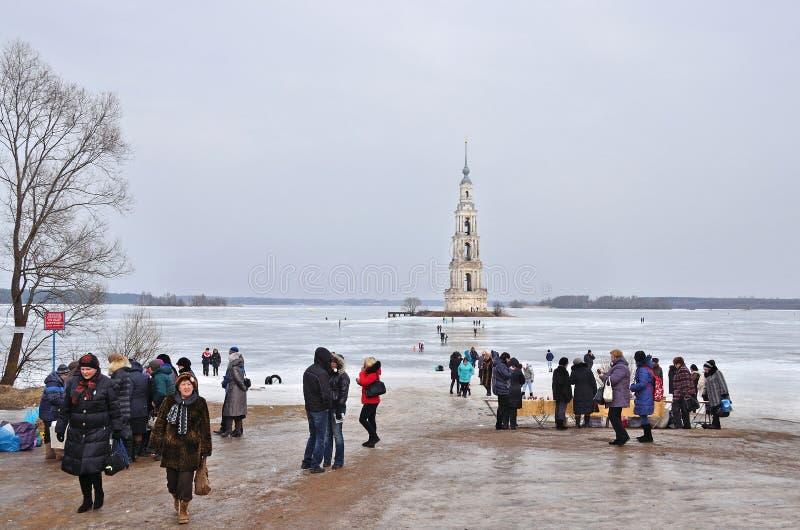 Kalyazin, Rússia, março, 02, 2014 Povos que andam perto da torre de sino de São Nicolau no inverno em Kaliazin no tempo nebuloso imagem de stock