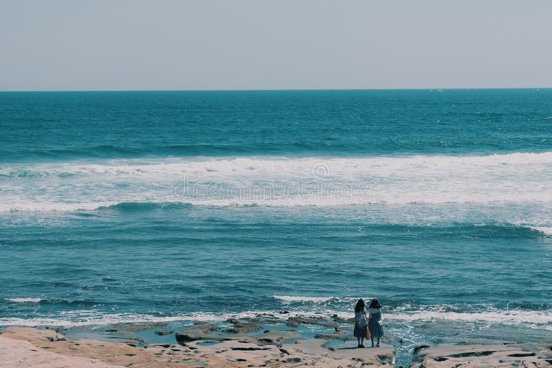 Kamakura sea. Two tourists are looking at something in the sea,summer background concept, kamakura, landscape, japan, nature, beautiful, travel, water, sky, blue royalty free stock photo