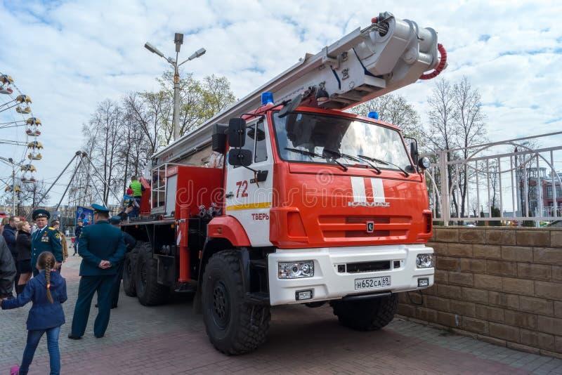 Kamaz-Löschfahrzeuge mit Leitern an der Unterseite eines Feuerwehrmanns herein lizenzfreies stockbild