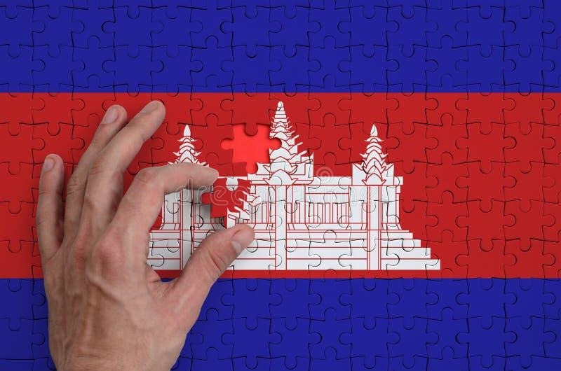 Kambodża flaga przedstawia na łamigłówce którą składać uzupełnia mężczyzna ` s ręka, zdjęcie stock