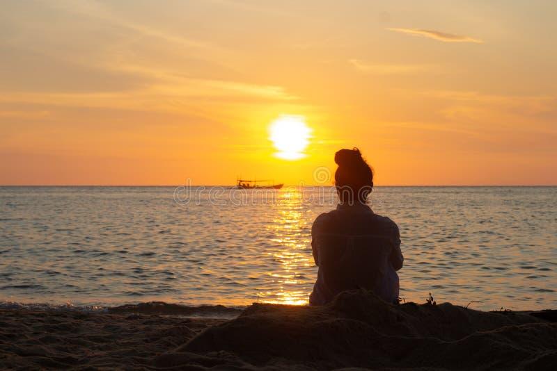 Kambodjansk asiatisk kvinna som h?ller ?gonen p? solnedg?ngen & fartyget vid havet arkivbilder