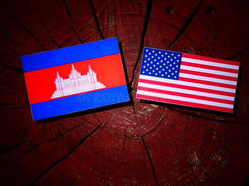 Kambodjansk flagga med USA flaggan på en trädstubbe royaltyfri fotografi
