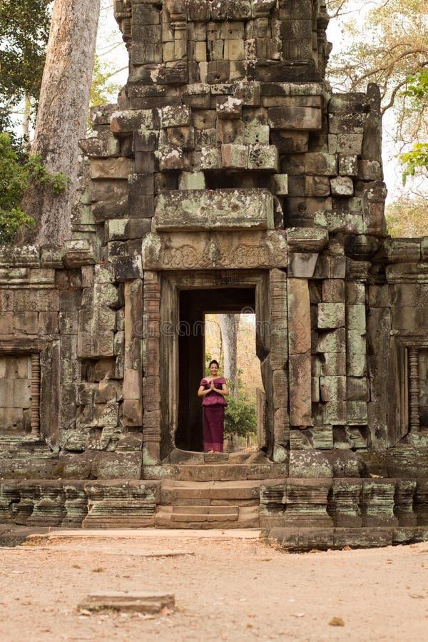 Kambodjansk flicka i en khmerklänninganseende i dörröppningen av en forntida vägg i Angkor Thom royaltyfri bild