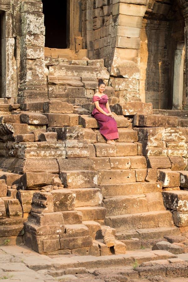 Kambodjansk flicka i en khmerklänningsammanträde på den Bayon templet i den Angkor staden royaltyfria bilder