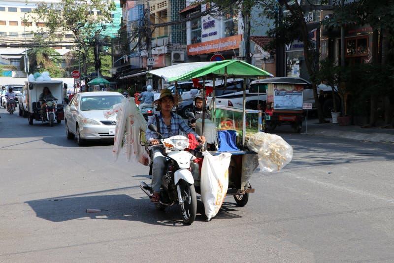 Kambodjansk man av ritten för sockerrörfruktsaftgatuförsäljare motorcykeln för tre hjul av hans kiosk som kan flytta sig till oli royaltyfria foton