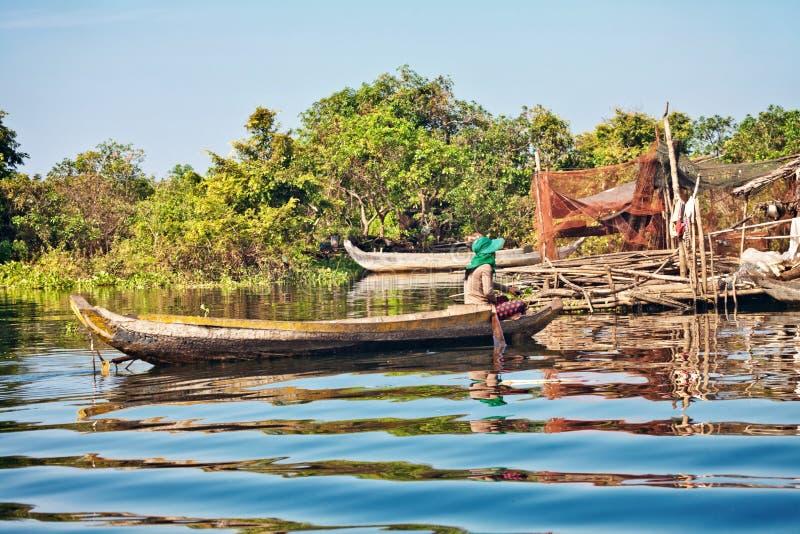 Kambodschanische Frau, die in ein Boot schwimmt lizenzfreie stockfotos