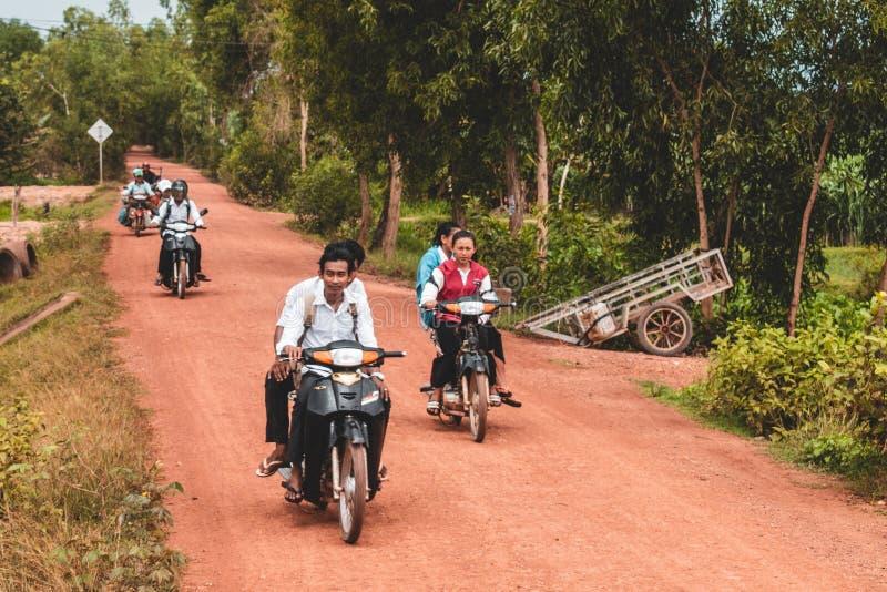 Kambodschanische Leute, die Roller durch ländliches Kambodscha fahren lizenzfreie stockfotografie
