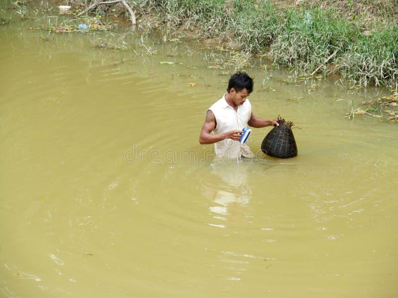 Kambodschanischer Mann im Schmutzwassersee stockfotos