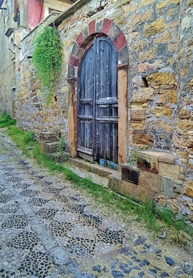 Rustic arched wooden door on stone wall and stone paved alley with shapes. Kambos area, chios island, Greece, rustic arched wooden door on stone wall and stone royalty free stock image