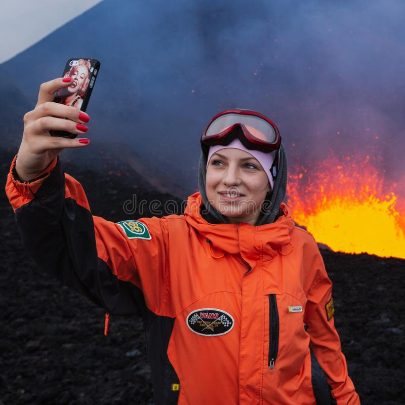 Young girl hipster photographed selfie on background lava lake erupting volcano. KAMCHATKA PENINSULA, RUSSIA - JULY 27, 2013: Eruption Tolbachik Volcano on royalty free stock image
