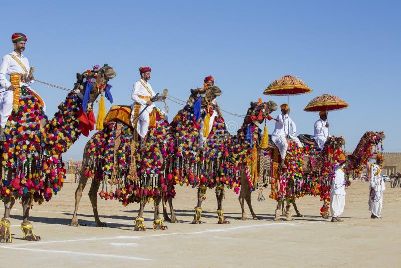 Kameel en de Indische mensen die traditionele Rajasthani-kleding de dragen nemen aan M. deel Woestijnwedstrijd als deel van Woest stock foto
