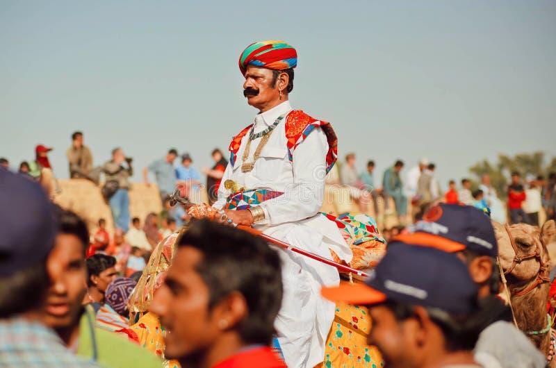 Kamelryttare i retro indiskt dräktdrev till och med folkmassan av den populära ökenfestivalen royaltyfri bild