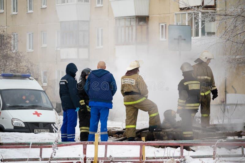 Kamensk-Uralsky Ryssland, Februari 10, 2018: Brandmän och doktorer i stället för brand, släckt brand går rök royaltyfri foto