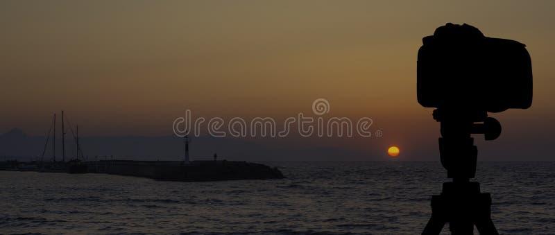 Kamera auf Stativ mit Meer und Sonnenuntergang im Hintergrund stockbilder