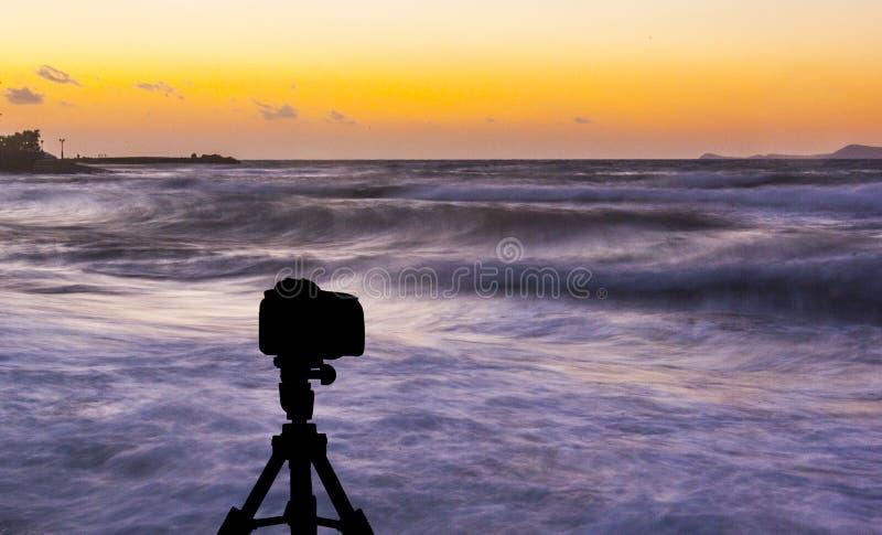 Kamera auf Stativ mit Meer und Sonnenuntergang im Hintergrund lizenzfreie stockfotografie