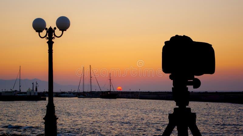 Kamera auf Stativ mit Meer und Sonnenuntergang im Hintergrund lizenzfreies stockfoto