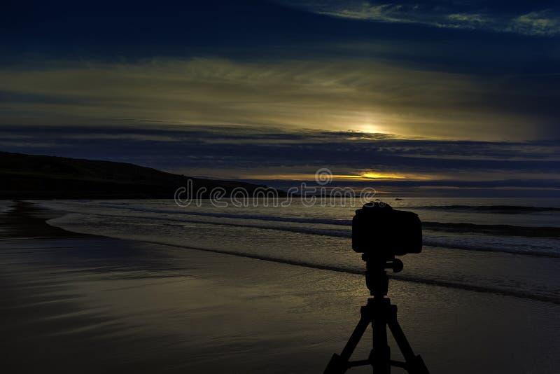 Kamera auf Stativ mit Ozean und Sonnenuntergang im Hintergrund lizenzfreies stockbild