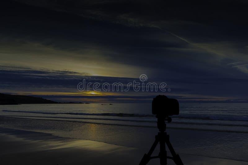 Kamera auf Stativ mit Ozean und Sonnenuntergang im Hintergrund stockfotografie