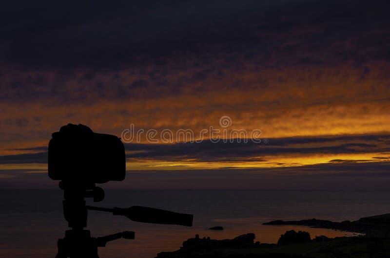 Kamera auf Stativ mit Ozean und Sonnenuntergang im Hintergrund stockfotos