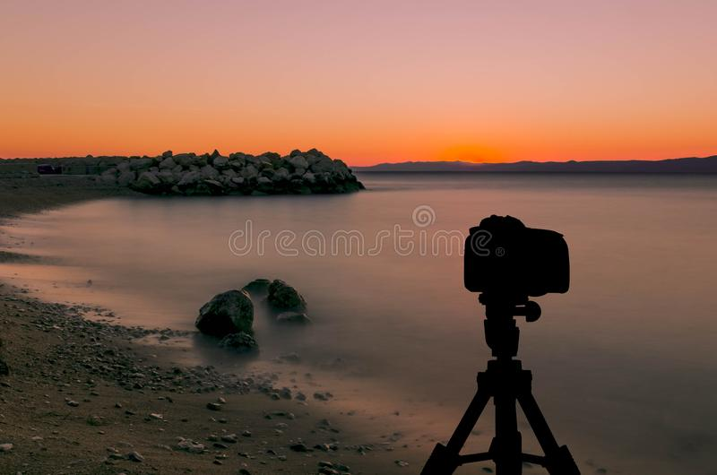 Kamera auf Stativ mit Ozean und Sonnenuntergang im Hintergrund lizenzfreie stockfotografie