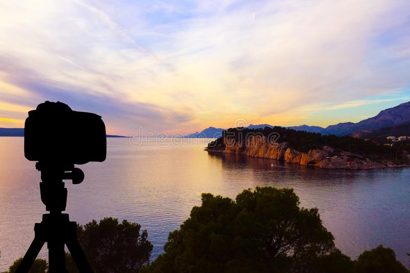 Kamera auf Stativ mit Ozean und Sonnenuntergang im Hintergrund/in Kroatien stockbild