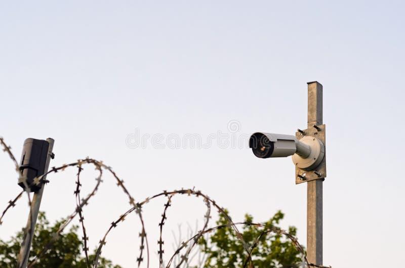 Kamera bezpiecze?stwa na s?upie Obserwacja perymetr ochraniający teren z drutem kolczastym fotografia stock